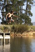 stock photo of jetties  - Boy Jumping From Jetty Into Lake - JPG