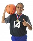 stock photo of preteens  - A happy preteen athlete supporting his basketball on his shoulder - JPG