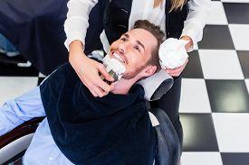 stock photo of barber razor  - Man getting beard shave in barber salon - JPG