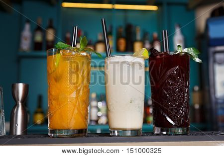 Closeup of three creative sweet exotic non-alcoholic party cocktails in restaurant at bar background. Glasses on bar table, refreshing drinks with straws.