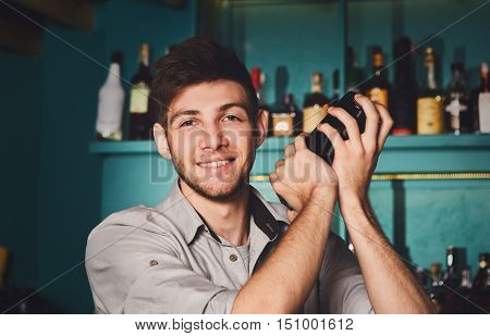 Young handsome barman in bar interior shaking and mixing alcohol cocktail. Professional bartender at work with shaker in hands