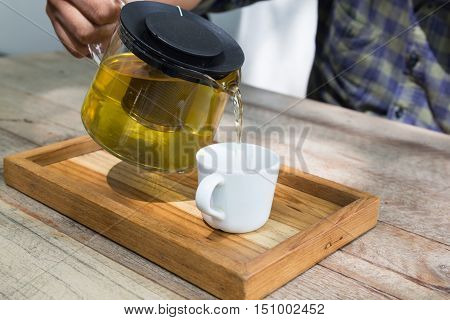 pouring hot tea into the white cup on wood table