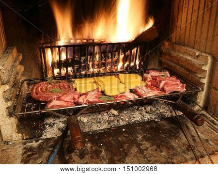 Raw Meat  Cooking In The Fireplace With A Warm Fire Lit