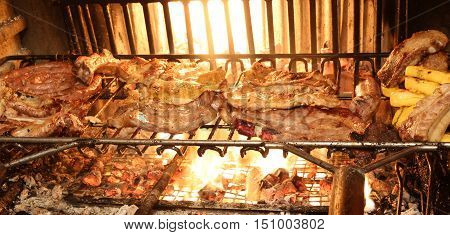 Cooking The Meat On The Grill In The Large Fireplace