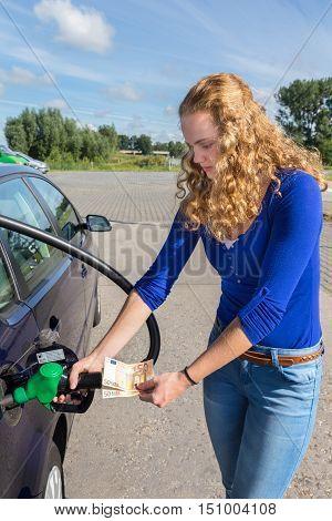 European woman refueling car tank with petrol