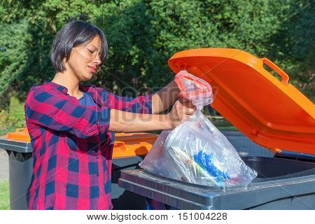 European woman throwing plastic garbage in container