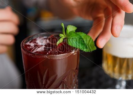 Closeup of healthy sweet berry non-alcoholic party cocktail at restaurant background. Refreshing drink with ice, blackberries and mint