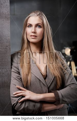 Portrait of attractive young blonde businesswoman standing arms crossed.
