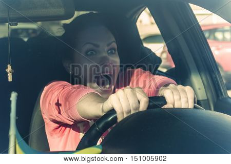 Brunette young woman sitting behind the wheel of the car and yells. Emotional intelligence concept.
