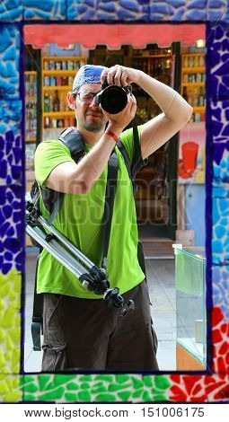 professional photographer with a blue bandanna and a tripod makes a selfie in a mirror with decorated frame