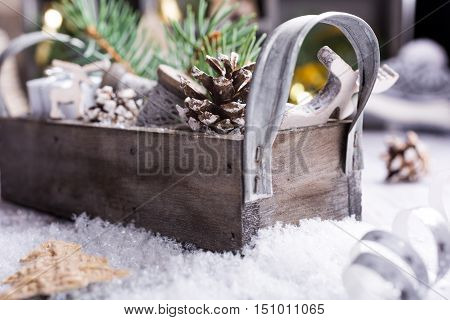 Christmas composition with wooden box with pinecone, gifts and decoration on snow. Christmas greeting card with copy space.
