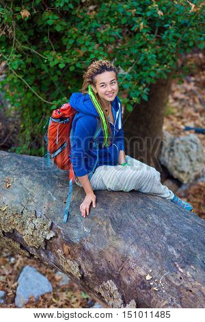 Cute smiling Girl with Day Backpack and sporty casual Clothing sitting on large fallen Tree Stalk in wild Forest Outdoors Sunlight