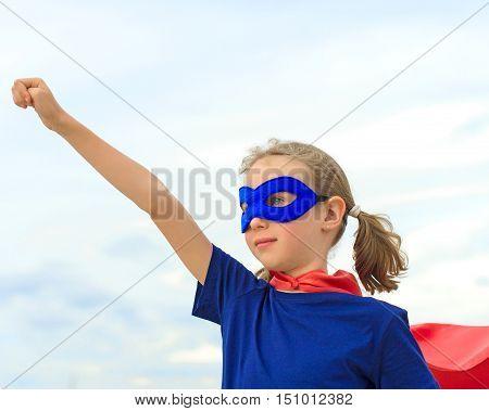 Superhero female kid against blue sky background.