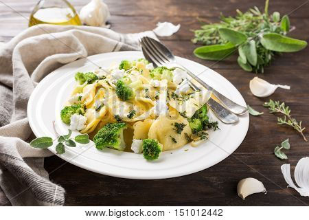 Plate of ravioli with broccoli, goat cheese and herbs on old wooden background. Italian healthy food concept.