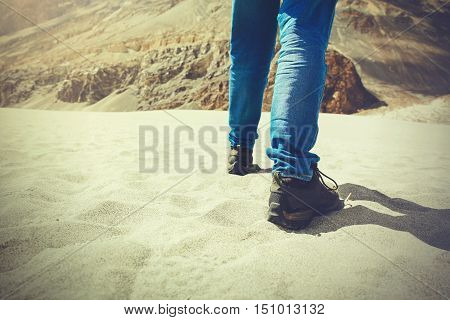 Traveler walking in the sand dune towards the hill - travel vacationrecreation and adventure (Vintage tone).