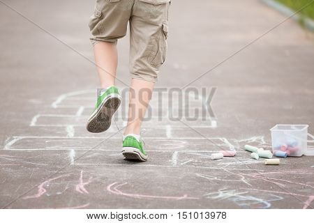 Closeup of boy's legs and hopscotch drawn on asphalt. Child playing hopscotch on playground outdoors on a sunny day. outdoor activities for children.