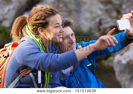Two Hikers Man and Girl with Dreadlocks Hair Style smiling taking self Portrait Photo with Camera of smart phone on Hike in Spring Time Forest