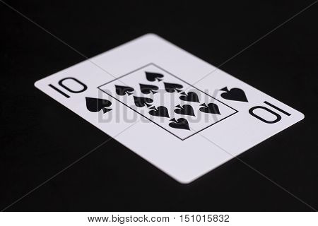 Ten of spades playing card on black background