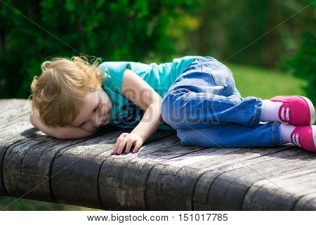 Cute and smilling little girl in the park in summer day