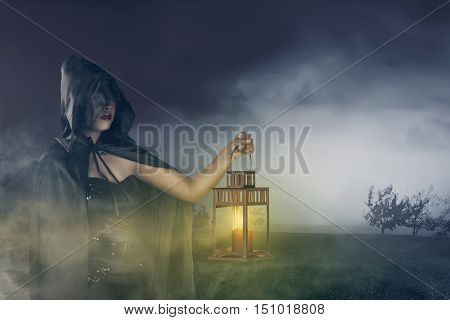 Beautiful Asian Witch Girl Holding A Lantern With A Cloak On His Head