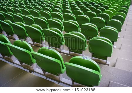 Green seating rows in a stadium with weathered chairs
