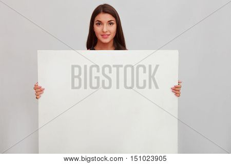 Woman showing copy space for product or text on open hand palm, smiling joyful and happy. Caucasian female girl presenting something isolated on white background. Copyspase for product or sign text
