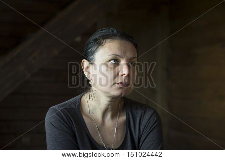 Low key portrait of a tired mature woman