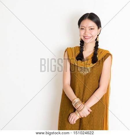Portrait of young mixed race Indian Chinese girl in traditional Punjabi dress smiling, standing on plain white background.