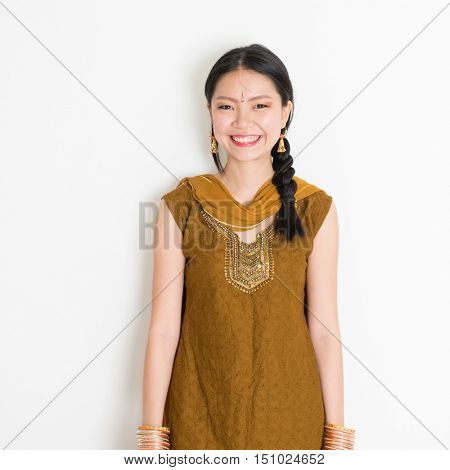 Portrait of young mixed race Indian Chinese female in traditional Punjabi dress smiling, standing on plain white background.