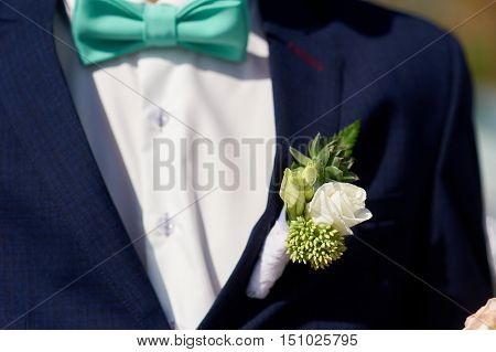 white wedding boutonniere of rose on Groom's jacket