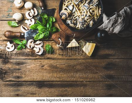 Italian style dinner. Homemade creamy mushroom pasta spaghetti in cast iron pan with Parmesan cheese, fresh basil leaves and pepper over old rustic wooden background. Top view, copy space, horizontal