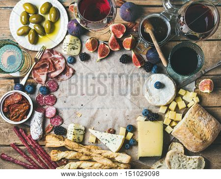 Food frame. Wine and snack set with various wines in glasses, meat variety, bread, green olives, figs and berries on wax paper over rustic wooden background, top view, copy space in center
