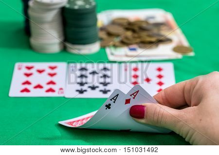 Poker chips and a hand with two aces against green felt