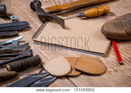 Set of tools notebook pencil for shoemaker on the wooden background.