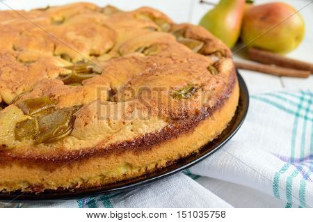 Home baked biscuit flavored pear charlotte cake with cinnamon. On a white wooden background. Close up