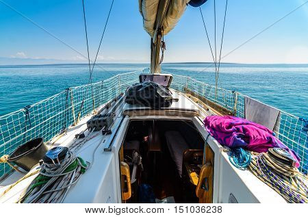 Front view of sailing boat on the sea. Bow side of yacht or sail boat gliding through calm sea in Adriatic sea on the sunny day.