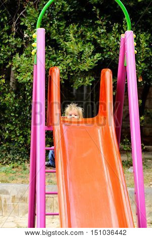 Cute baby boy child with curly blond hair plays on slide on child playground on summer day