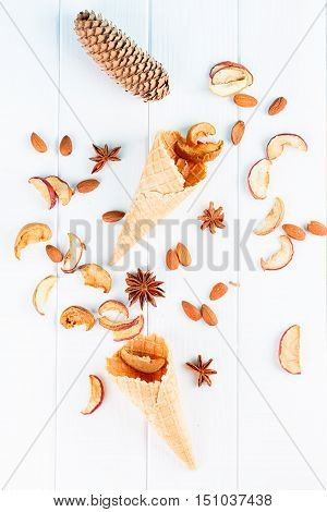 autumn still life - waffle cups cones dried apples on the white Board top view