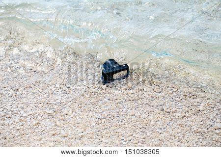 Photo camera digital fell under sea crystal pure water on pebble beach