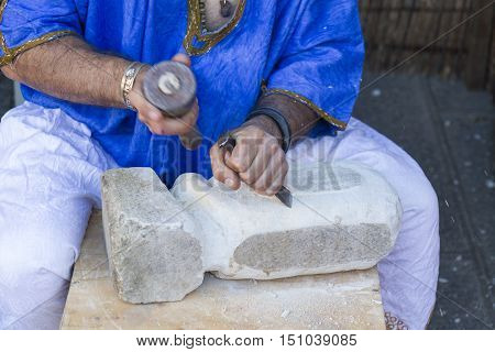 Man working hard stone with its outdoor tools