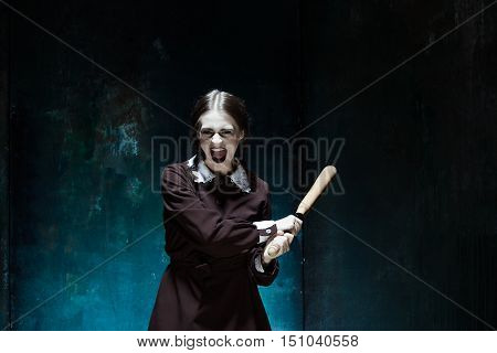 Portrait of a young girl with baseball-bat in school uniform as killer woman against school board . The image in the style of Halloween