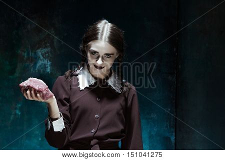 Portrait of a young girl with a piece of raw meat. Girl in school uniform as killer. The image in the style of Halloween