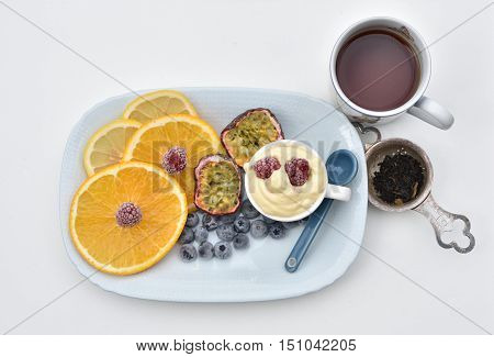 Healthy flatlay with tea, blueberry, raspberry, passionfruit, orange, lemon on a plate, mango and passionfruitmousse in a cup.
