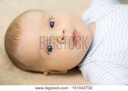 Cute baby boy blond infant with blue eyes in romper lies on his back on beige bed cover