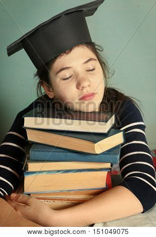 intelligent teen girl in graduation cap wiht book pile sleeping tired of studying