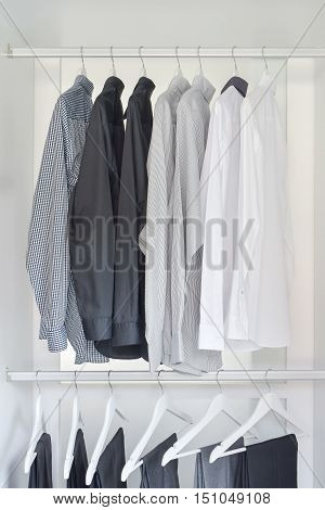 row of white gray black shirts with pants hanging in wooden wardrobe