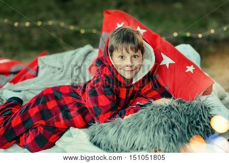 outdoors little boy lying in bed in red pajamas with toys and fruit