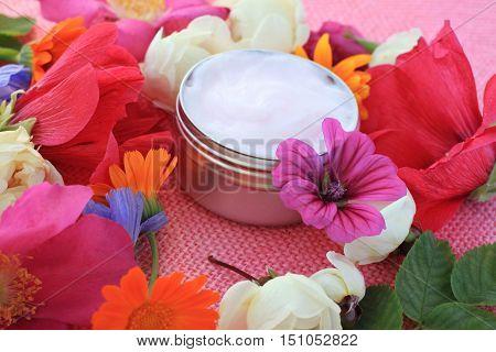 Herbal facial cream in sample jar, fresh bright flowers. Botanical hair and skin care.