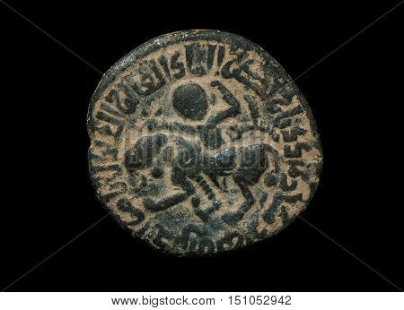 Ancient Bronze Islamic Coin With Image Of Person Riding The Lion Isolated On Black