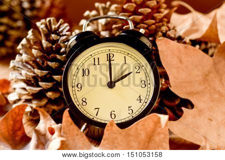 closeup of an alarm clock adjusting backward one hour at the end of the summer time, surrounded by dry leaves and pinecones